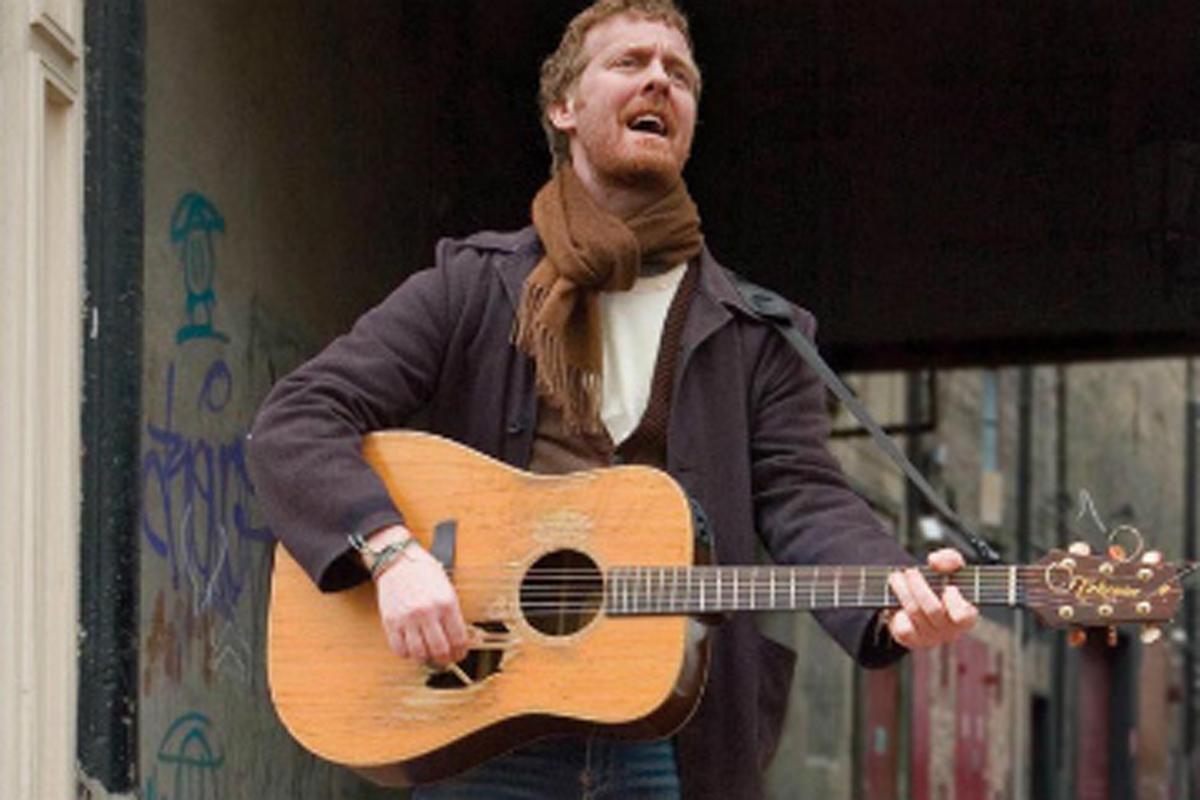 路上で弾き語りをする男性の画像